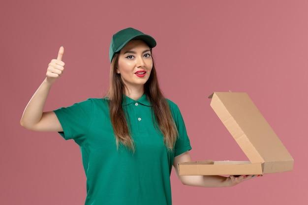 ピンクの壁のサービス制服配達の女の子に食品配達ボックスを保持している緑の制服の正面図女性宅配便