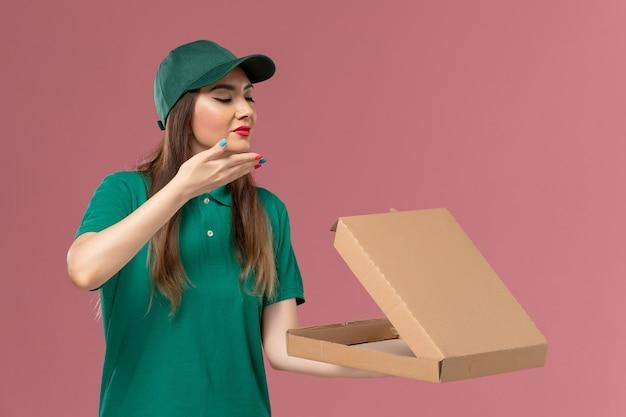 ピンクの壁に臭いがする食品配達ボックスを保持している緑の制服を着た正面図の女性宅配便会社サービス制服配達
