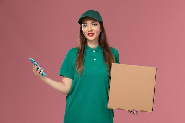 ピンクの壁の会社のサービスの制服の配達の仕事で電話を使用して食品配達ボックスを保持している緑の制服の正面図女性宅配便