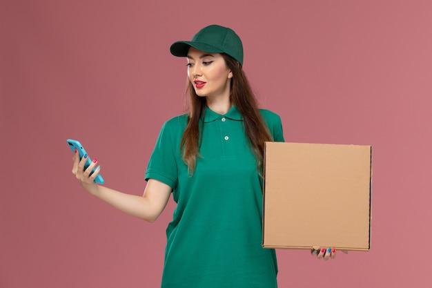 Вид спереди курьер-женщина в зеленой форме держит коробку для доставки еды по телефону на розовой стене.