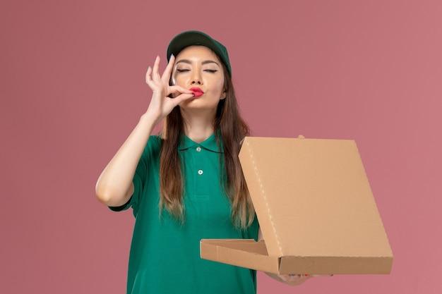 ピンクの壁のサービス制服配達女の子会社の食品配達ボックスを保持し、開く緑の制服の正面図女性宅配便