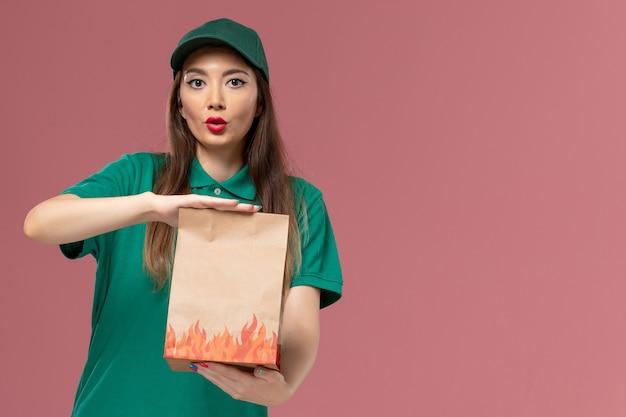 ピンクの壁のサービス制服配達の女の子に紙の食品パッケージを保持している緑の制服の正面図の女性の宅配便