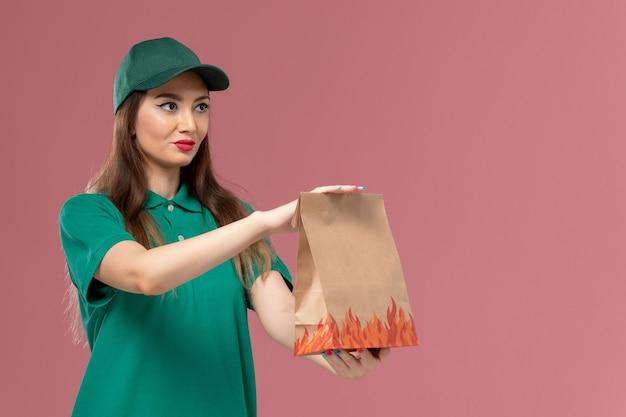 밝은 분홍색 벽 서비스 유니폼 배달에 종이 음식 패키지를 들고 녹색 제복을 입은 전면보기 여성 택배