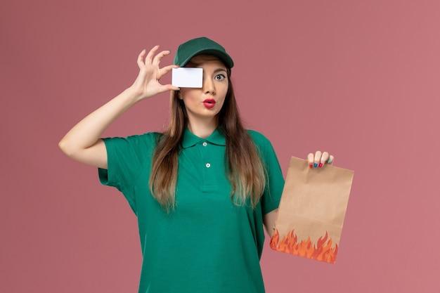 淡いピンクの壁サービスの制服配達の仕事で白いカードと食品パッケージを保持している緑の制服の正面図の女性の宅配便