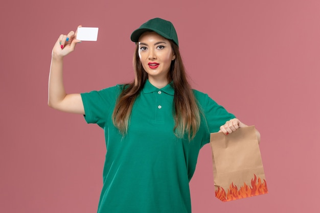 ピンクの壁に白いカードと食品パッケージを保持している緑の制服を着た正面図の女性宅配便サービス制服配達仕事