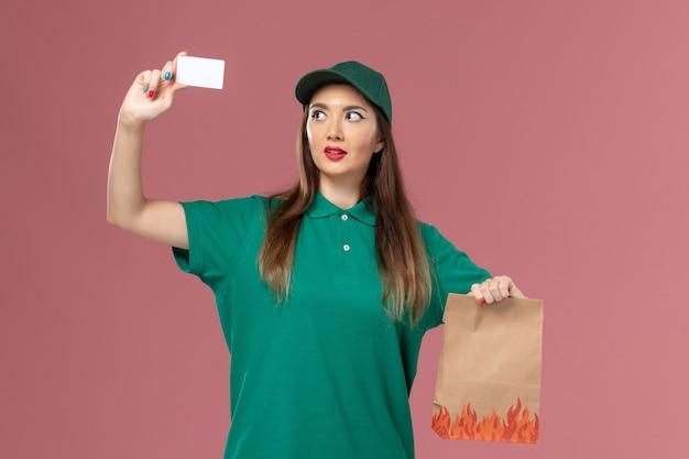 ピンクの壁に白いカードと食品パッケージを保持している緑の制服を着た正面図の女性の宅配便サービス制服配達労働者