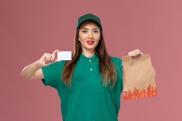 ピンクの壁のサービスの制服配達の仕事で白いカードと食品パッケージを保持している緑の制服の正面図の女性の宅配便