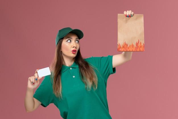ピンクの壁のサービス制服労働者の配達の仕事で白いカードと食品パッケージを保持している緑の制服の正面図の女性の宅配便