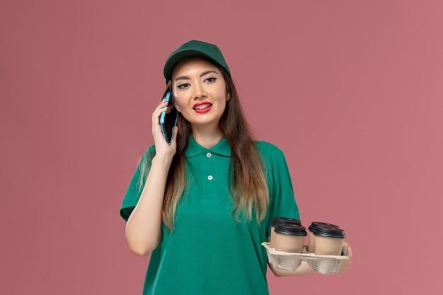 電話で話し、ピンクの壁のサービス制服配達の仕事で配達コーヒーカップを保持している緑の制服を着た女性の宅配便の正面図