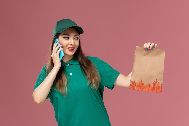 電話で話し、ピンクの壁のサービスの制服配達の仕事で食品パッケージを保持している緑の制服を着た正面図の女性の宅配便