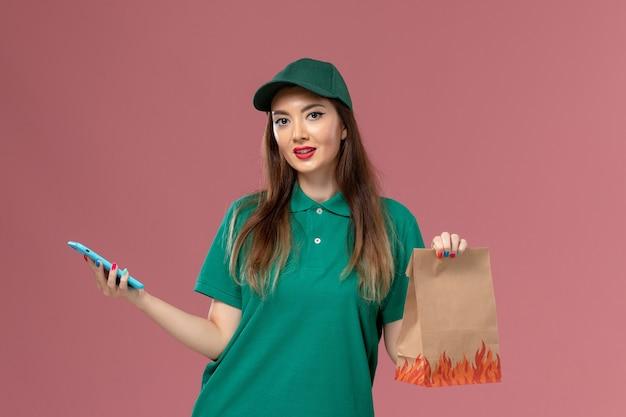 電話を使用し、ピンクの壁に食品パッケージを保持している緑の制服を着た正面図の女性宅配便