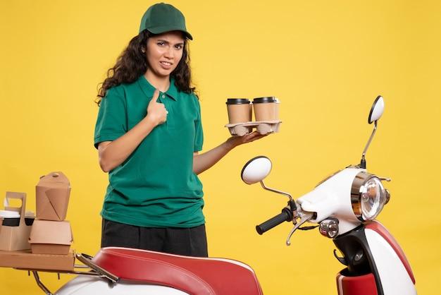 Вид спереди женщина-курьер в зеленой форме с кофе на желтом фоне цветной работник службы доставки еды женщина