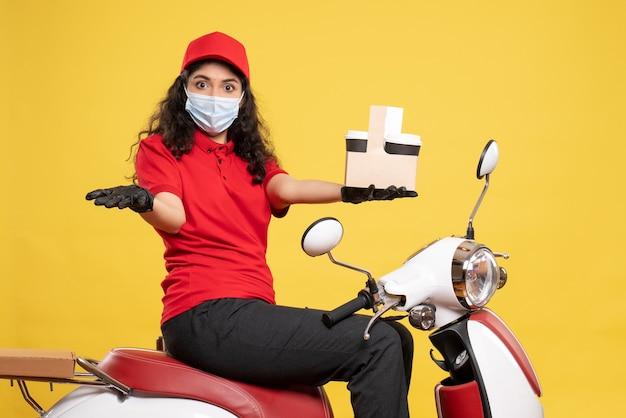 노란색 배경 covid- 작업 배달 유니폼 작업자 서비스 작업에 커피 컵과 마스크에 전면보기 여성 택배