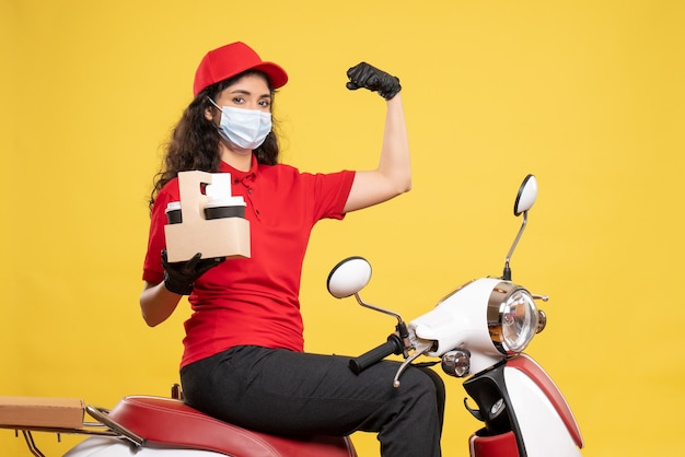 노란색 배경 covid- 작업 배달 유니폼 작업자 서비스 작업 전염병에 커피 컵과 마스크에 전면보기 여성 택배
