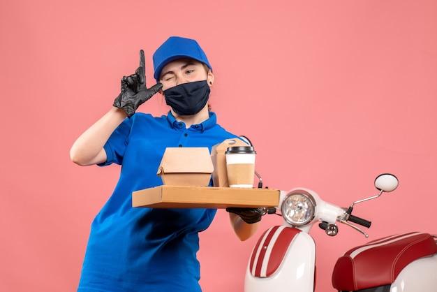 Вид спереди женщина-курьер в маске с доставкой кофе и еды на розовом столе пандемия covid - доставка униформы работника службы занятости