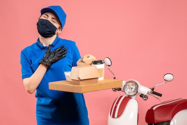 ピンクの配達コーヒーと食べ物とマスクの正面図の女性の宅配便