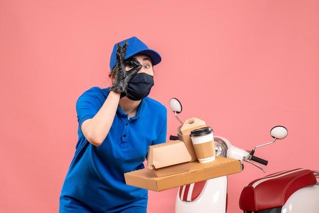 Женский курьер в маске с доставкой кофе и еды на розовом фоне, вид спереди