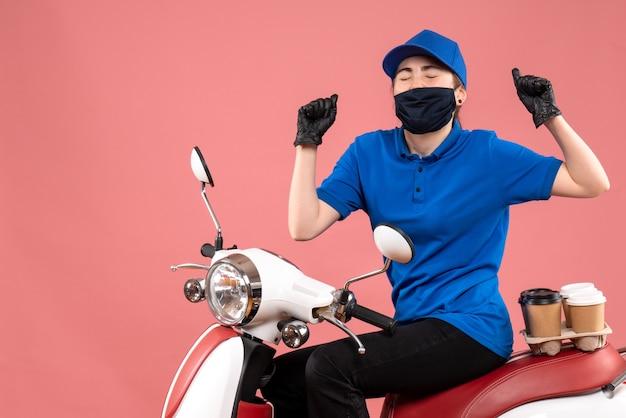 Женщина-курьер в маске с доставкой кофе радуется на розовом фоне, вид спереди