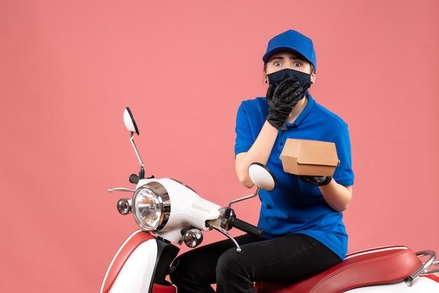 ピンクの小さな食品パッケージとマスクの正面図の女性の宅配便