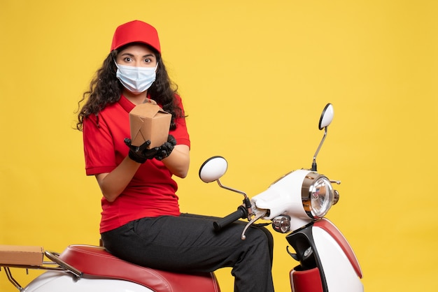 노란색 배경 서비스 전염병 작업자 유니폼 covid- 작업 배달에 작은 음식 패키지와 마스크에 전면보기 여성 택배