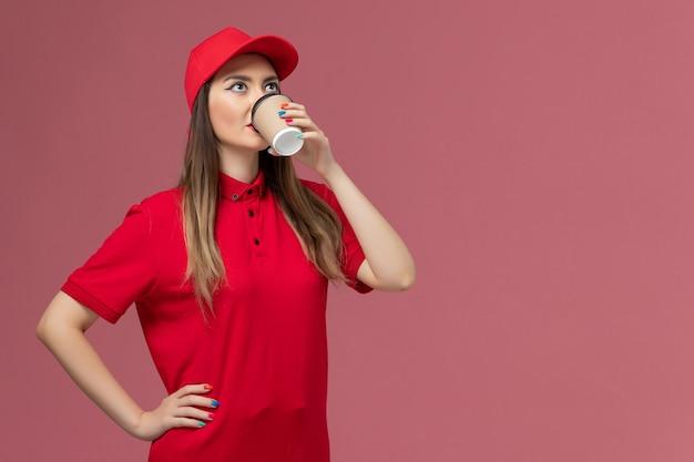 빨간색 유니폼과 케이프 핑크 배경 서비스 배달 유니폼 작업 노동자에 커피를 마시는 전면보기 여성 택배