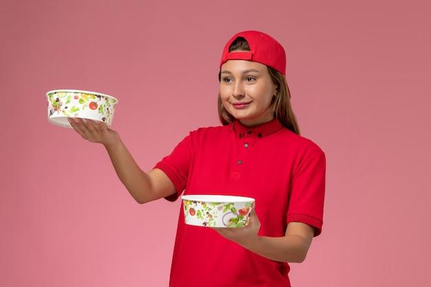 赤い制服を着た正面図の女性の宅配便とピンクの壁に配達ボウルを保持している岬、制服配達ジョブサービス