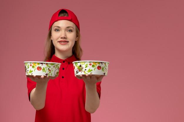 赤い制服を着た正面図の女性宅配便と淡いピンクの壁に笑顔で配達ボウルを保持している岬、サービス制服配達
