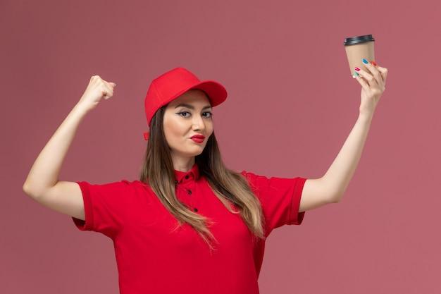 빨간색 유니폼과 케이프 배달 커피 컵을 들고 분홍색 배경 서비스 작업 배달 작업자 유니폼에 flexing 전면보기 여성 택배
