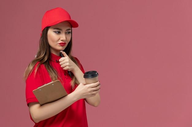 빨간 유니폼과 케이프 배달 커피 컵 메모장과 밝은 분홍색 배경 서비스 배달 유니폼에 펜을 들고 전면보기 여성 택배