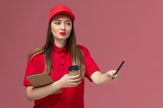 빨간색 유니폼과 케이프 핑크 배경 서비스 배달 유니폼에 배달 커피 컵 메모장과 펜을 들고 전면보기 여성 택배