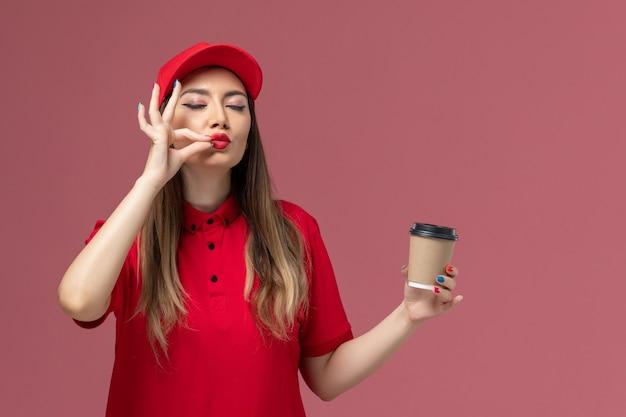빨간색 유니폼과 케이프 분홍색 배경에 배달 커피 컵을 들고 전면보기 여성 택배 서비스 배달 유니폼 작업 노동자 소녀