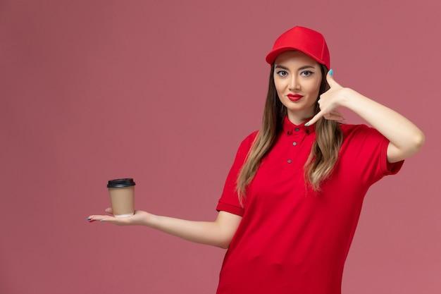 빨간색 유니폼과 케이프 분홍색 배경 서비스 배달 유니폼 작업에 배달 커피 컵을 들고 전면보기 여성 택배