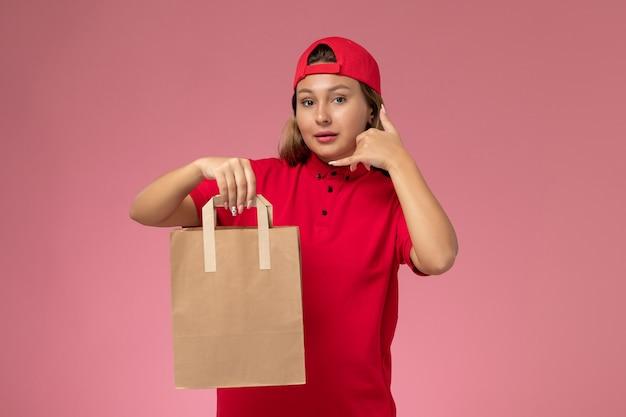 Вид спереди женщина-курьер в красной униформе и накидке, держащая посылку с доставкой на светло-розовом фоне.