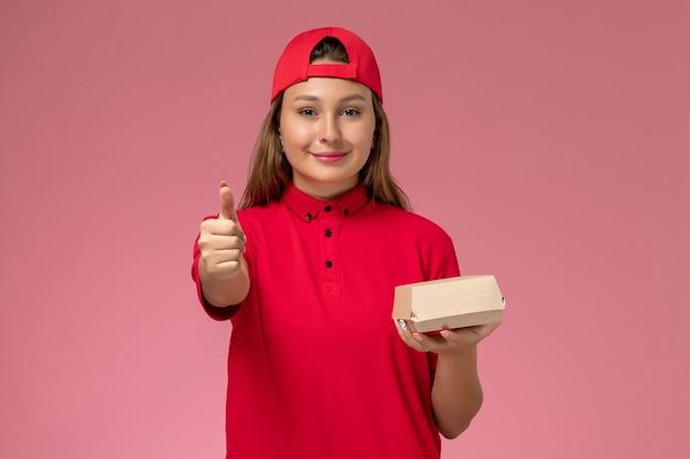 赤い制服とピンクの背景に配達食品パッケージを保持している岬の正面図の女性の宅配便制服配達サービス会社の仕事