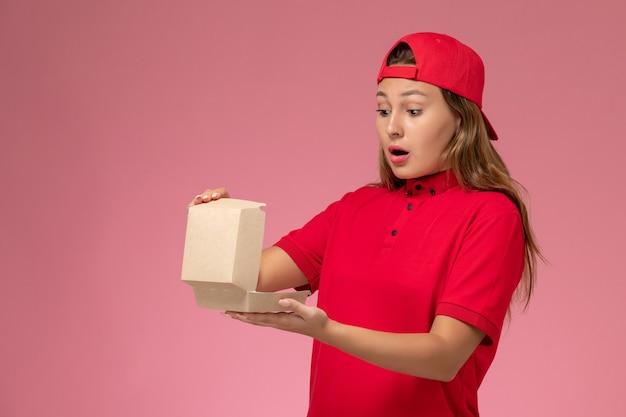 赤い制服を着た正面図の女性宅配便と薄ピンクの壁にそれを開く配達食品パッケージを保持している岬、制服配達サービス会社