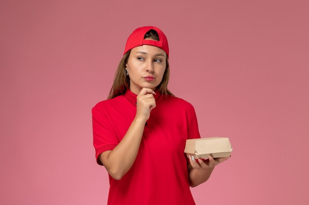 赤い制服を着た正面図の女性宅配便とピンクの壁を考えて配達食品パッケージを保持している岬、制服配達サービス会社の仕事