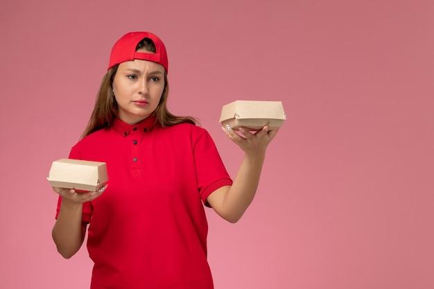 赤い制服とケープの正面図の女性宅配便は、配達食品パッケージを保持し、淡いピンクの壁、制服配達サービスのジョブワーカー会社を考えています