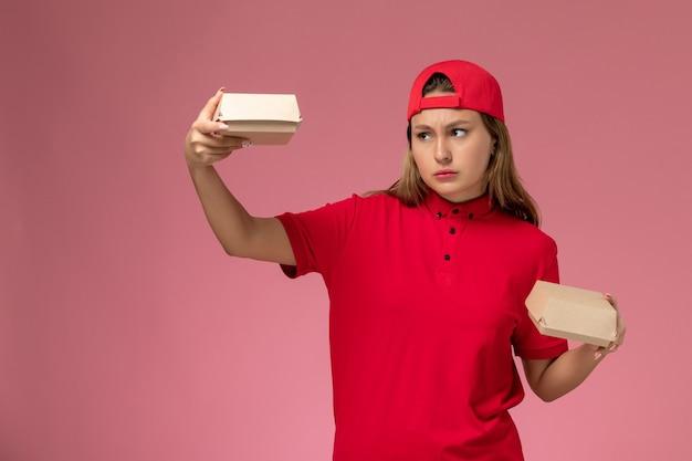 赤い制服を着た正面図の女性の宅配便と淡いピンクの壁に配達食品パッケージを保持している岬、制服配達サービス会社の仕事の仕事