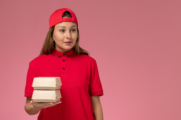 赤いユニフォームと薄ピンクの壁に配達食品パッケージを保持している岬の正面図の女性の宅配便、制服配達サービス会社の仕事