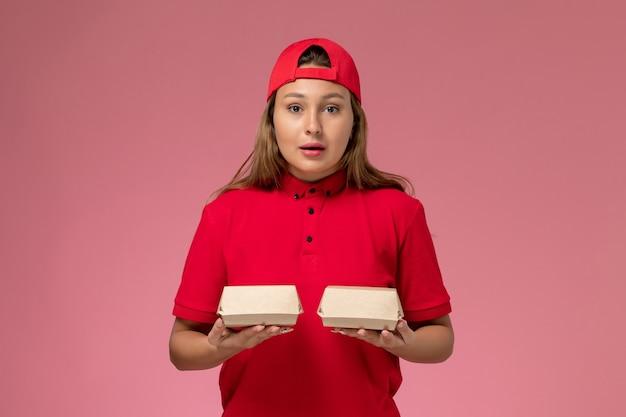 赤い制服を着た正面図の女性の宅配便と淡いピンクの壁に配達食品パッケージを保持している岬、制服配達サービス会社のジョブワーカー