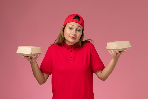 赤い制服を着た正面図の女性宅配便と淡いピンクの壁に配達食品パッケージを保持している岬、制服配達サービス会社の仕事