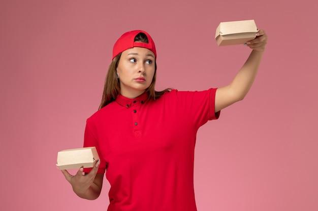 赤い制服と薄ピンクの壁に配達食品パッケージを保持している岬の正面図の女性の宅配便、制服配達サービス会社の労働者