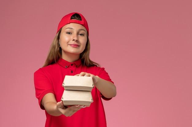 赤い制服を着た正面図の女性宅配便と淡いピンクの壁に配達食品パッケージを保持している岬、制服配達サービス会社
