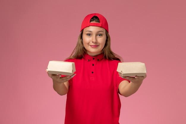 赤い制服を着た正面図の女性宅配便と淡いピンクの壁に配達食品パッケージを保持している岬、制服配達サービスの労働者会社
