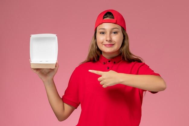 Женщина-курьер в красной форме и плаще, держащая пустой пакет с доставкой на светло-розовой стене, компания службы доставки униформы