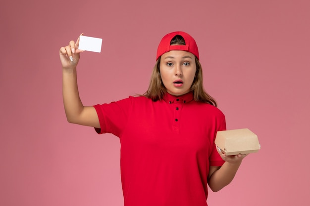 ピンクの壁に小さな配達食品パッケージとカードを保持している赤い制服と岬の正面図の女性の宅配便、制服配達サービスの労働者