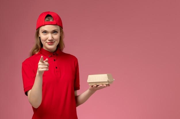 밝은 분홍색 벽, 배달 서비스 회사 제복 작업에 지적 작은 배달 음식 패키지를 들고 빨간 유니폼과 케이프의 전면보기 여성 택배