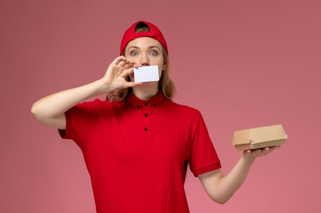 ピンクのデスクサービスの仕事の制服の配達に白いプラスチックカードと小さな配達食品パッケージを保持している赤い制服と岬の正面図の女性の宅配便
