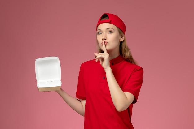 ピンクの壁に小さな空の配達食品パッケージを保持している赤い制服と岬の正面図の女性の宅配便、配達サービス会社の制服の仕事の労働者