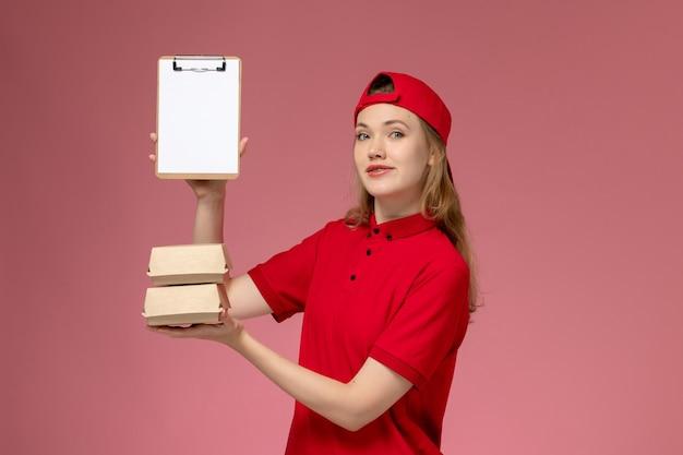 밝은 분홍색 배경 서비스 유니폼 배달 작업에 메모장과 작은 배달 음식 패키지를 들고 빨간 유니폼과 케이프의 전면보기 여성 택배